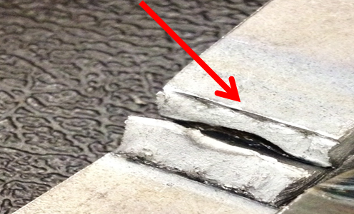 The arrow points to the root of the joint.  Being able to see the edge of the top piece is indicative of lack of root fusion.