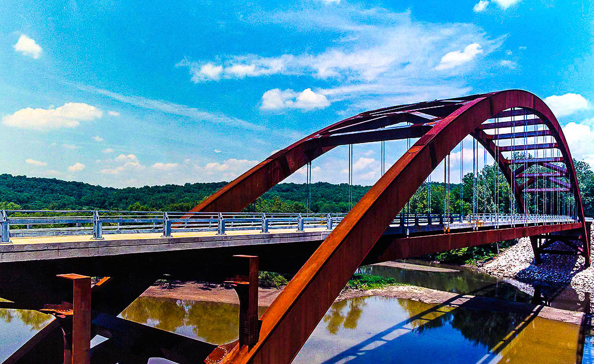 Bridges like the Paper Mill Road Bridge use weathering steel which does not require paint in order to protect from the damaging effects of corrosion due to atmospheric exposure.