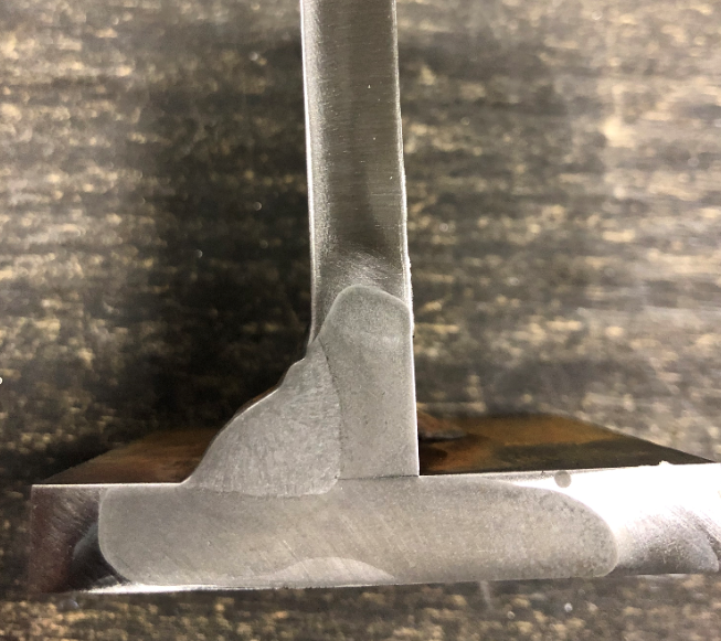 "FCAW weld done in the 3F positions with upward progression. Leg size of 1/2"" achieved by weaving. Macroetch shows fusion to the root and beyond."